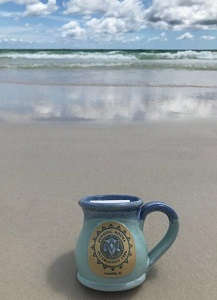 Sundog Pot Belly Mug on a smooth, sunny beach in front of emerald waves.