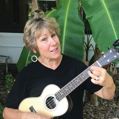 Fran Bussard holds a ukelele in front of a banana tree in a front yard.